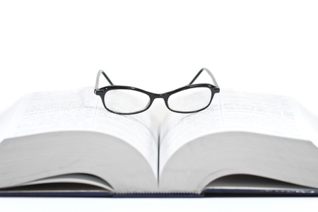 Closeup of reading glasses on the book isolated on white background photo