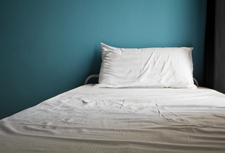 pillow case: Messy white bed and one pillow , light blue wall in the morning