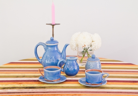 tea or coffee set on table with colorful line fabric in gray wall room photo
