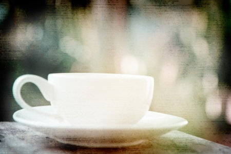 a white cup of black coffee in garden background