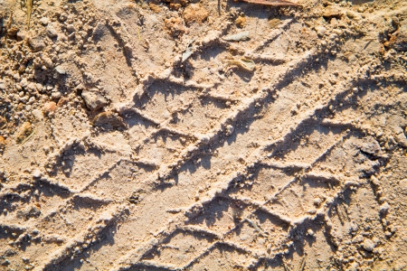 a photo of close up wheel tracks print detail on soil land photo