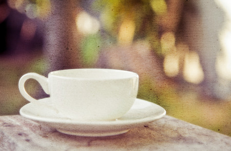 a white cup of coffee in garden background photo