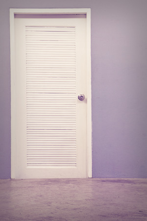 A photo of empty wall with a white door Stock Photo