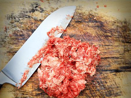 lamentation: una foto di carni macinate e coltello su tagliere