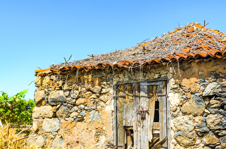 This cottage stone-built with a dilapidated door stands in a vineyard in Santa Ursula in Tenerife. Stock Photo