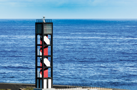 The red and white lighthouse of Puerto de la Cruz on Tenerife on the Atlantic Ocean is Directly. He is protected by a concrete wall.