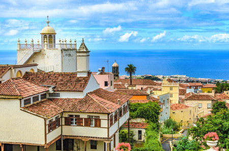 View from the old town of La Orotava goes over the roofs with red tiles of the historic houses and churches to Puerto de la Cruz and the Atlantic Ocean. everywhere are Grne plants.