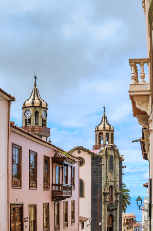 View from the old town of La Orotava goes over the rooftops with the red roof tiles of the historic houses and churches to Puerto de la Cruz and the Atlantic Ocean. Everywhere are green plants. Stock Photo