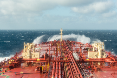breaking waves: Oil tanker steering forward during stormy weather with breaking waves - stock photo