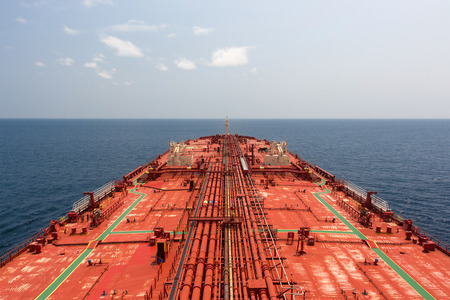 Oil tanker red deck under blue sunny sky. View from monkey deck.