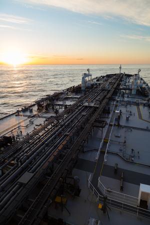 Vertikale Bild von Rohöltanker im Ozean, wenn Sonnenuntergang.