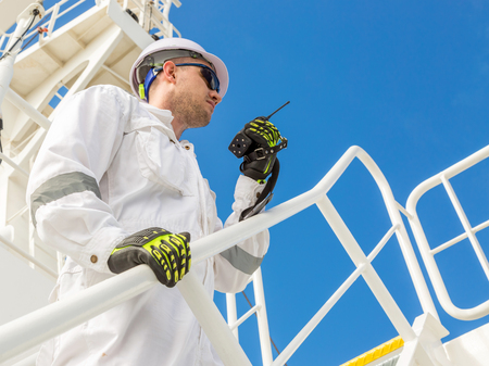 Engineer in white helmet and workwear with VHF under blue sky Stock Photo