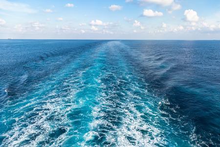 seaway: Wake on blue sea surface under cloudy sky.