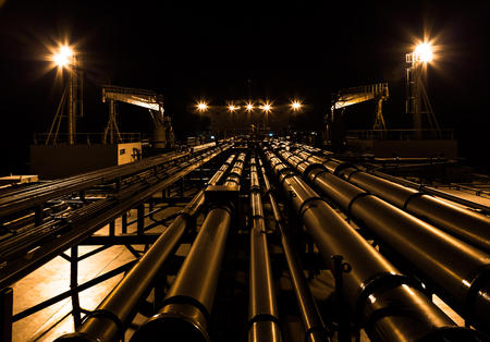 superstructure: Night view of oil tanker deck view from fore to aft.