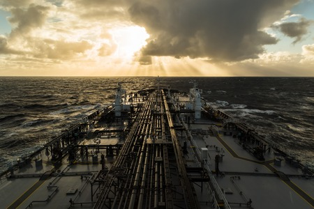 Crude oil tanker deck under cloudy sky during sunset