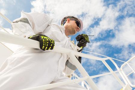 workwear: Engineer in white workwear speaking by VHF