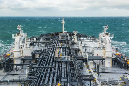 Deck of crude oil tanker forward part with cargo pipeline.
