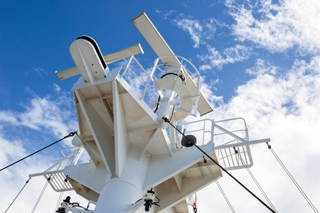 Sattelite communication antenna and radar mast on the top deck of the ship. Stock Photo