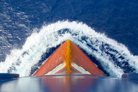 Red rusty bulb of a tanker in the blue sea. Stock Photo