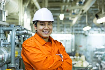 Glimlachende Aziatische ingenieur in witte helm in industriële ruimte. Stockfoto