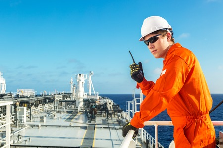 Deck officer using radio on the deck of oil tanker.