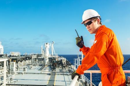 Dekofficier met behulp van radio op het dek van de olietanker. Stockfoto