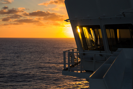 superstructure: View of sunset from navigation bridge under cloudy sky.