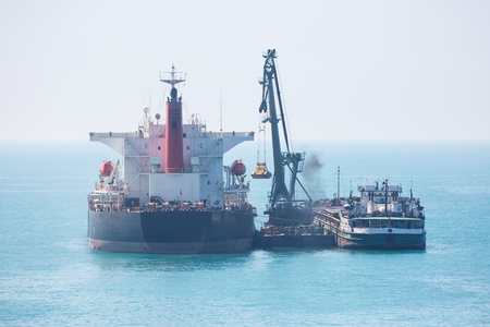 Dry cargo vessel transferring a cargo at sea.