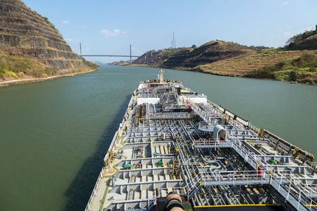 Small grey color oil tanker steaming through the Panama Canal.