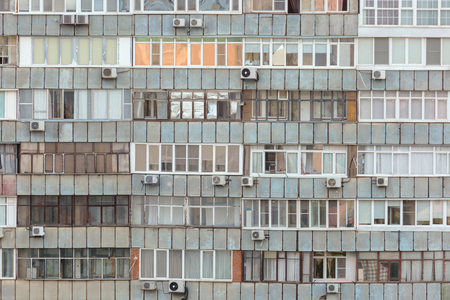Background of old apartment building with a lot of windows and air conditioners. Stock Photo