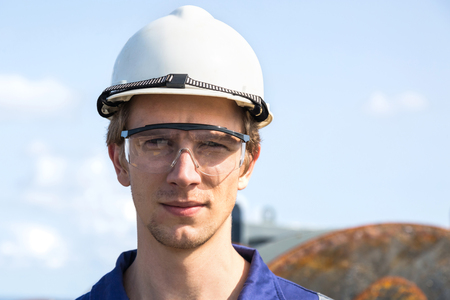 Portrait of a sad young European engineer in a white helmet and safety goggles.