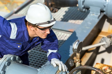 The engineer checks the pressure in the pipe of the cargo system of a oil tanker. Stock Photo