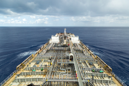 Oil product carrier underway at sea under cloudy sky.