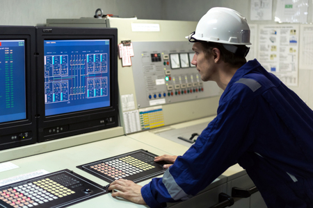 Young engineer in a cargo control room of a oil tanker.