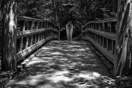 traverse: Shadows Over Wooden Bridge with Sculpture Stock Photo