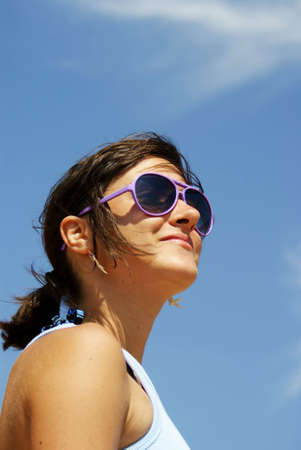 Portrait of a young woman smiling that wears sunglasses and looking somewhere far away Stock Photo - 7688857