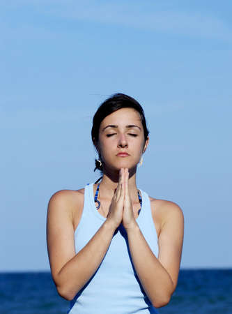 inner peace: Portrait of a young woman meditating near the sea and finding inner peace Stock Photo