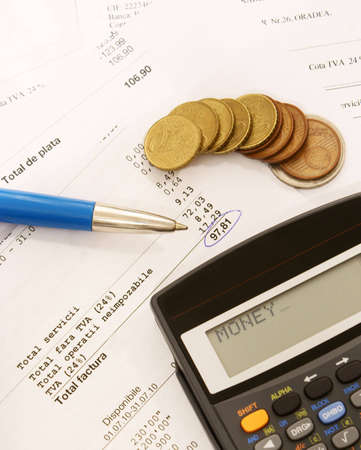 A table full of bills with a pen, some coins and a calculator that displays the word money Stock Photo - 7904028