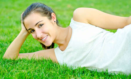cheerfull: Young girl resting on grass smiling beautifully