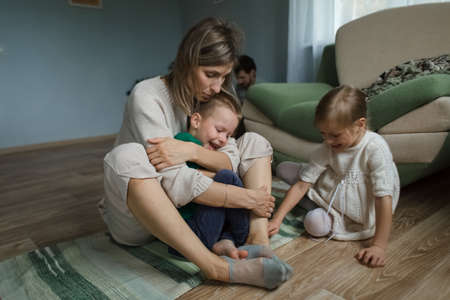 Mom at home sitting on the floor hugs and plays with the children. 版權商用圖片