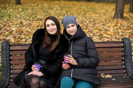 Two girls in the park talk on a bench with a phone and a glass.