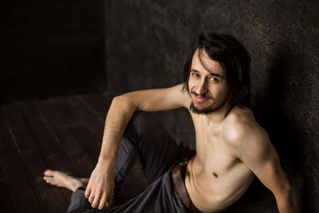 Skinny man without T-shirt sits looking at camera from below, beard mustache. Фото со стока