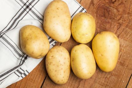 servilleta de papel: Las patatas y la servilleta sobre una mesa de madera