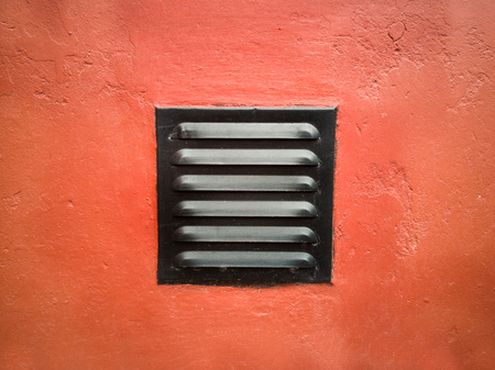 Ventilation grill on a red wall