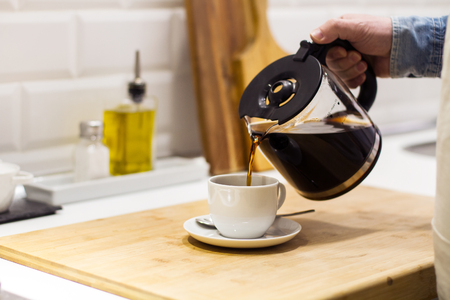 Man serving a filtered coffee in the kitchen