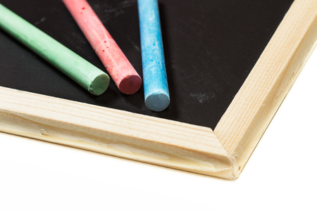 Colored chalks and a chalkboard Imagens