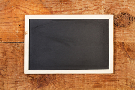 A clean chalkboard on a wooden background