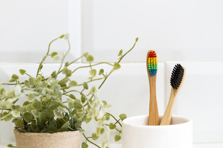 Bamboo toothbrushes in a ceramic glass in front of a tiled wall 免版税图像