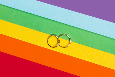 Two gold rings on a gay pride flag