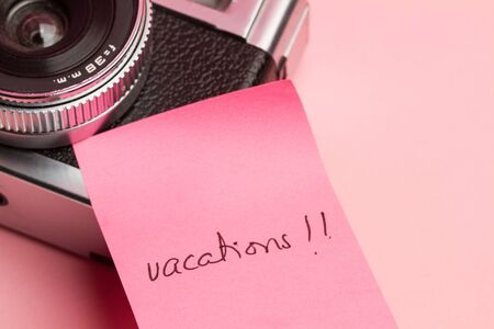 An old photo camera with a pink adhesive note with vacaction word Banco de Imagens